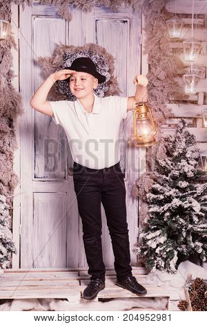 A 10 years boy staying at dorstep, looking ahead and holding lantern in his hand at Christmas