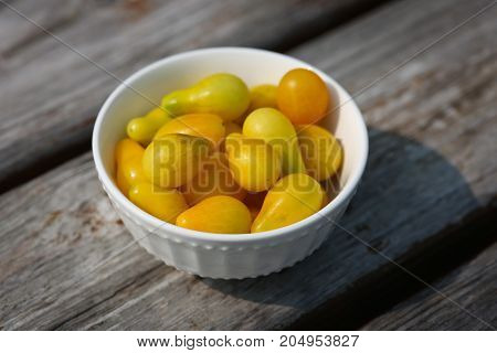 Heirloom yellow pear tomatoes in a white bowl.