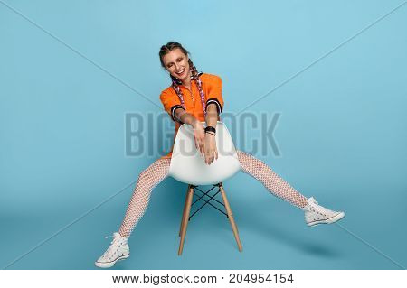 Young vivacious woman in dress and sneakers with braids posing cheerfully on chair in studio.