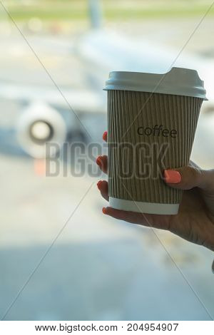 Cup Of Coffee In Airport's Business Lounge With Aircraft