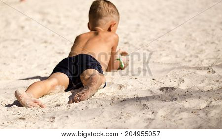 Feet of a boy playing in the sand .