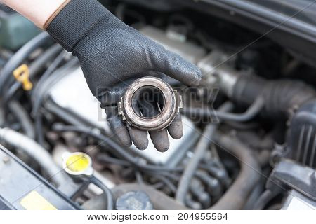Auto mechanic wearing protective work gloves holding old clutch release bearing over a car engine