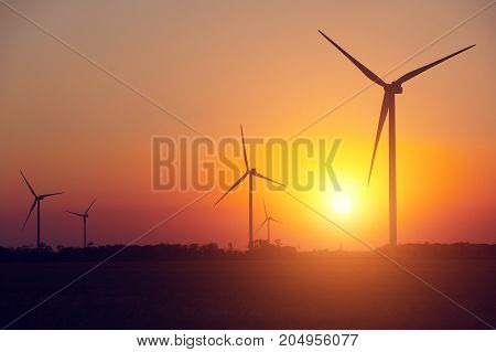 Wind power generation, Wind turbines on farmland with sunset