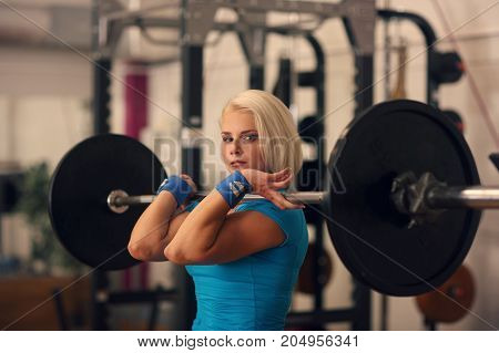 Bodybuilding. Strong Fit Woman Exercising With Barbell. Girl Doing Squats With Big Weights