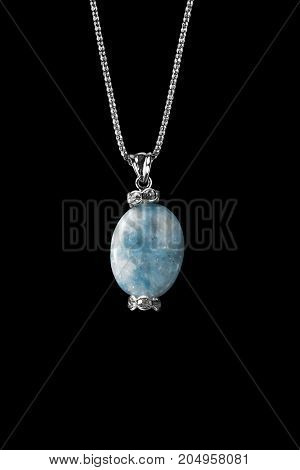 Vintage blue crystal pendant with diamonds on silver chain isolated over black