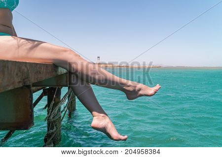 Young Female Legs Hang From The Pier Over The Sea Water