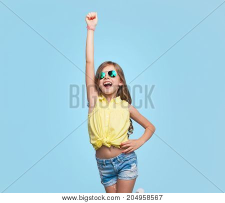 Little girl in sunglasses and casual clothing holding hand up looking victorious on blue.