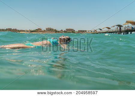 the girl swims in the sea on a back and enjoys a cool. her hair beautifully develop in water. There is a wish to plunge together in her into this atmosphere.