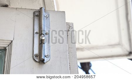 Stainless still Latch on the door has copy space roof white color at terrace of house.