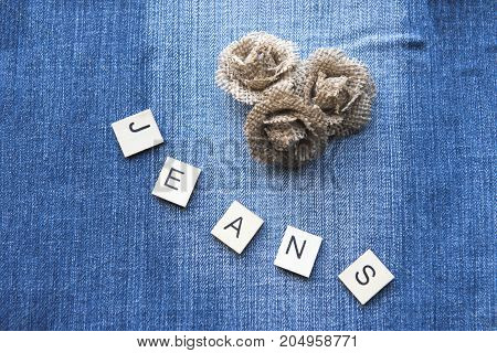 Denim background with hessian flowers and the word jeans spelt out