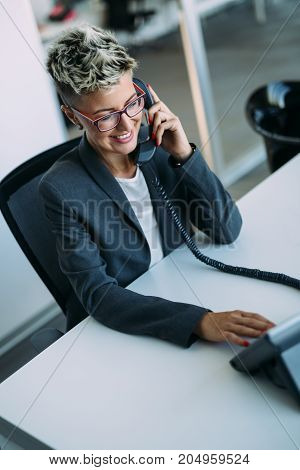 Portrait of busy female architect talking on phone in office