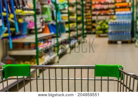 View From Shopping Trolley Into Abstract Blurred Supermarket Aisle Background