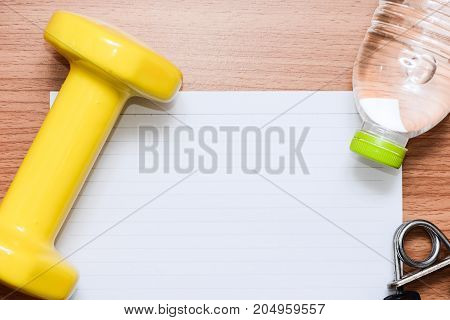 White line paper with sport equipments to plannig your health on brown wooden table top view