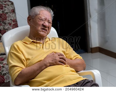Older Asian men sitting on a chair at living room with heart attacks.Both old man's hands on breast because of hard breathing Face old man with pain caused by heart disease.
