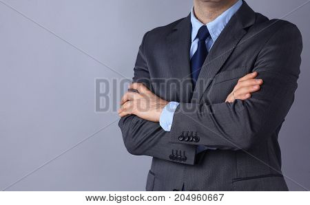 Young businessman standing with arms crossed on gray background.