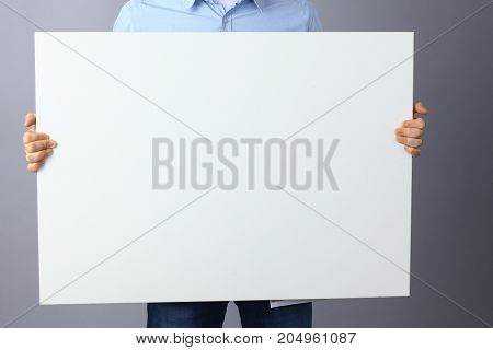 Businessman holding a blank board, standing on gray background.