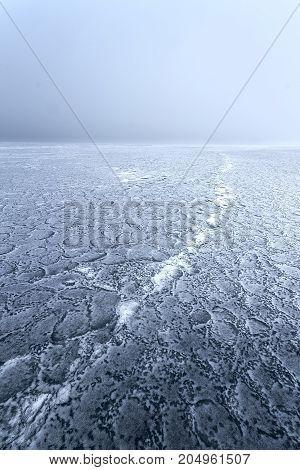 mist on a frozen lake / ice patterns on misty lake in early winter