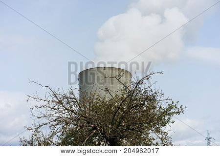 nuclear power plant cooler chimney with tree in front pollution nature risk