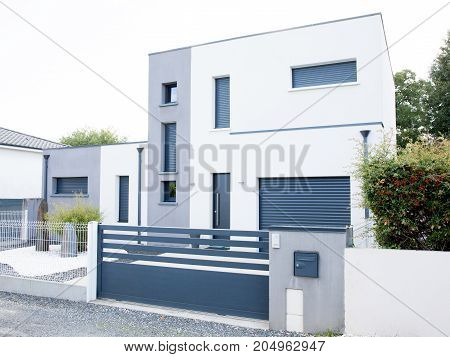 Modern House Has A Beautiful Lawn In Front Of The House And Garage From The Left Side That Has Concr