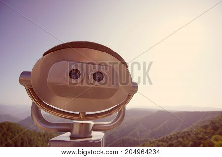 Coin Operated binocular viewer next to the mountain and the forest.