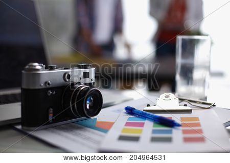 Laptop and camera on the desk with folder.