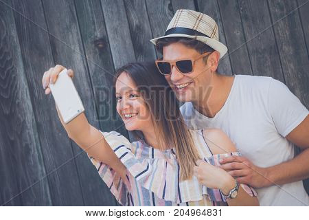 Young modern hipster couple taking selfie with smart phone against wooden wall. Love and technology concepts