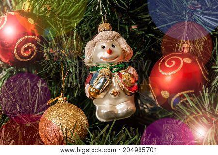 Christmas decoration snowman and balls on Christmas tree. Selective focus on snowman