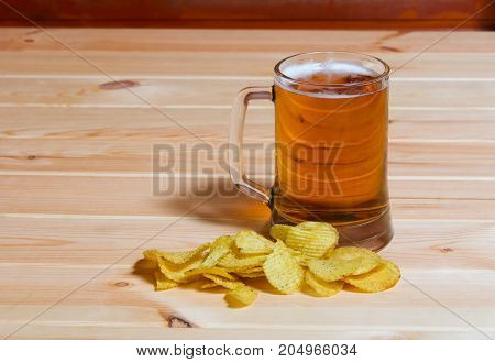 Mug of beer and potato chips on wooden table