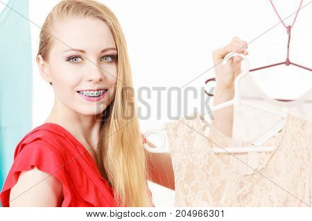 Happy smiling woman standing next to short white dress hanging on clothes hanger picking summer clothing outfit.