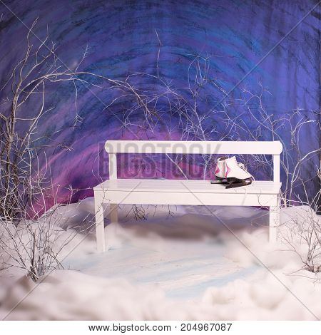 Studio shot of white bench with ice skates on it