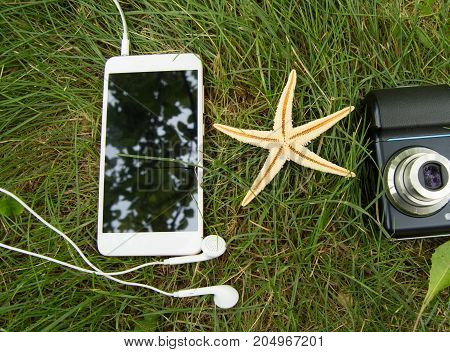 Plan Your Beach Holidays And Travel On The Grass With The Phone, Headphones, Starfish