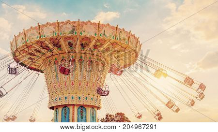 Carousel Ride Spins Fast In The Air At Sunset - Vintage Filter Effects - A Swinging Carousel Fair Ri