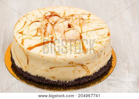 The cake with caramel on white wooden table