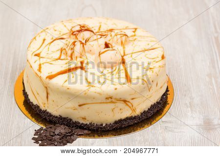 The cake with caramel and chocolate on white wooden table