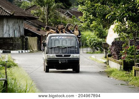 School bus carrying school girls back to their home. January 11 2014 - Trunyan Bali Indonesia