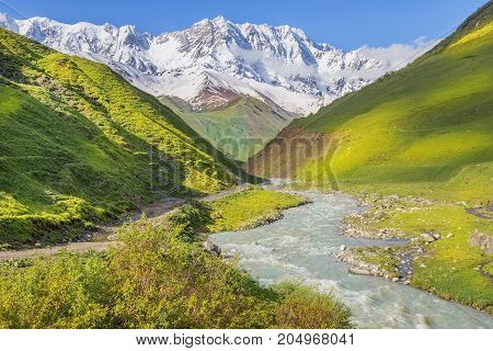 rough mountain stream and snow-capped peaks of the Caucasus Mountains in Upper Svaneti, Greater Caucasus Mountain Range in Georgia