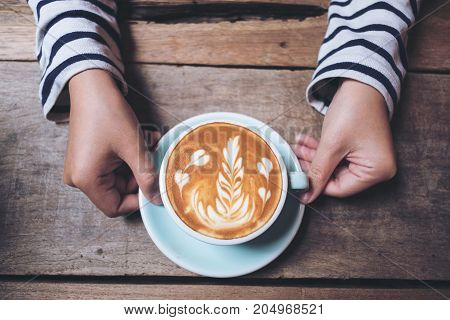 Top view image of woman's hands holding and showing a blue cup of hot latte coffee with latte art on wooden vintage table