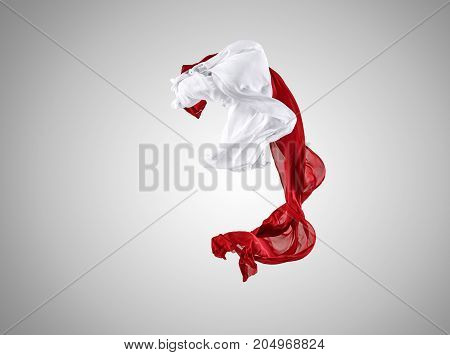 Smooth elegant transparent red and white cloth separated on gray background. Texture of flying fabric.