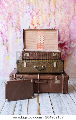 pyramid of several vintage suitcases on a pink background toned picture close-up shallow depth of field
