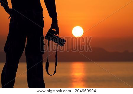 Silhouette of a photographer holding professional camera on the beachRed sky sunrise background