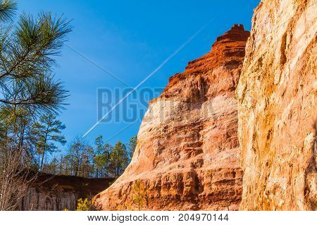 Red loamy wall of Providence Canyon with trees on the background of clear sky with contrail USA