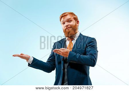 Portrait of a business man presenting something on blue background. Studio shot.