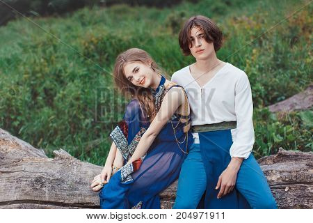 Young couple of elves in love siting on tree in magical forest outdoor on nature. Fairy tale love, relationship and magik people concept. Man and woman looking at camera