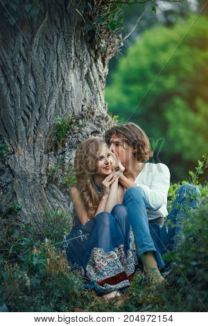 Young couple of elves in love sitting in magical forest agaist the big tree outdoor on nature. Fairy tale of love, relationship and magik people concept. Man whispering to smiling woman on an ear something
