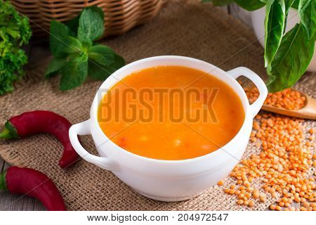 Lentil soup in a ceramic white bowl on a wooden background