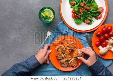 Unrecognizable woman eating rolls with carrot and broccoli on gray background. Healthy eating concept, organic vegetables top view.