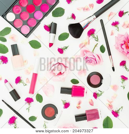 Feminine desk with woman cosmetics and pink flowers on white background. Flat lay, top view. Beauty background for woman