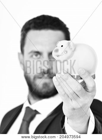 Piggybank In Hand Of Businessman In Suit And Tie