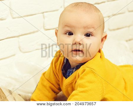 small baby boy with adorable curious face in yellow sweater laying on tummy on white brick wall background