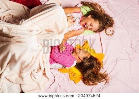 Childhood and happiness concept. Kids in pink pajamas fool around in bed. Children with happy faces lie on pink background top view. Schoolgirls have fun covered with white blanket
